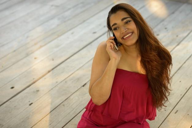 Glückliche junge schöne indische frau, die am telefon spricht, während sie auf holzboden sitzt