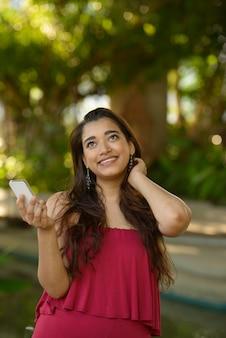 Glückliche junge schöne indische frau, die beim telefonieren im park denkt