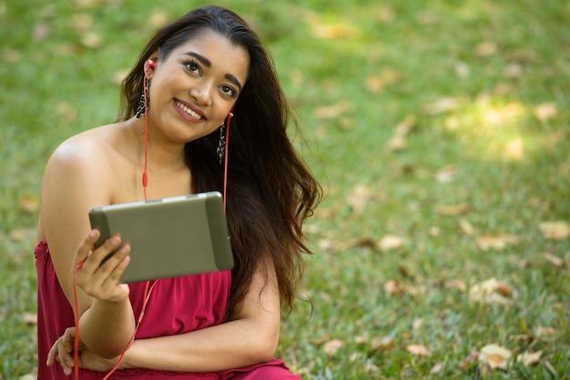 Glückliche junge schöne indische frau, die beim verwenden des digitalen tabletts am park denkt