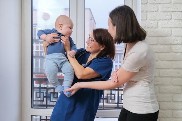 Glückliche junge schöne mutter, die mit kleinkindsohn spielt