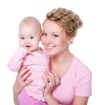 Glückliche junge schöne mutter mit attraktivem lächeln, das ihr baby hält -