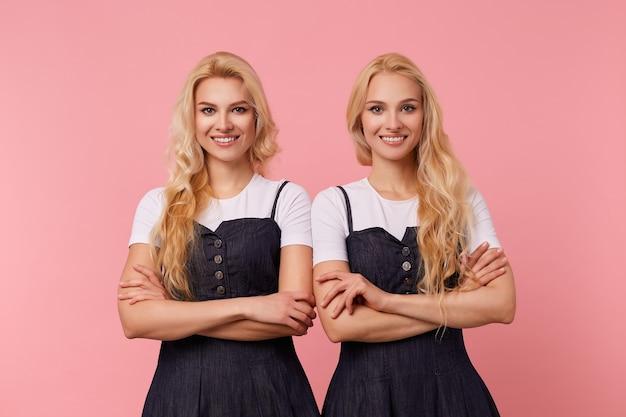 Glückliche junge schöne weißköpfige damen, die hände auf ihren brust falten, während sie kamera mit charmantem lächeln positiv betrachten, lokalisiert über rosa hintergrund