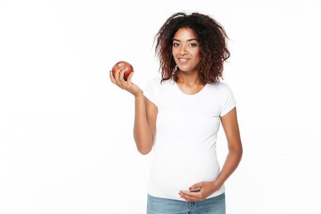 Glückliche junge schwangere afrikanische frau, die apfel hält.