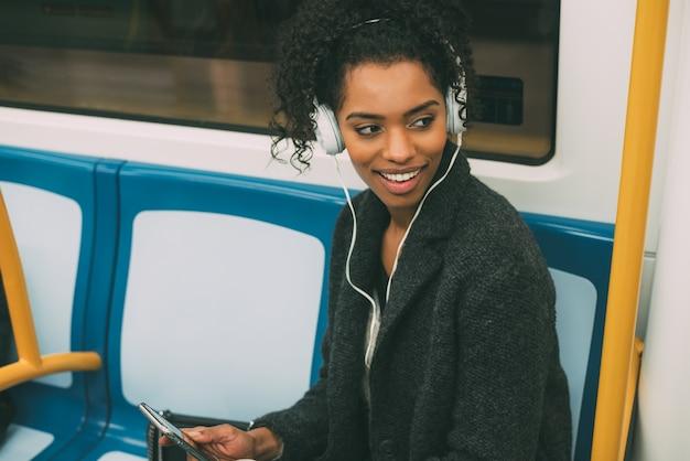 Glückliche junge schwarze frau, die innerhalb des untergrunds hört musik sitzt