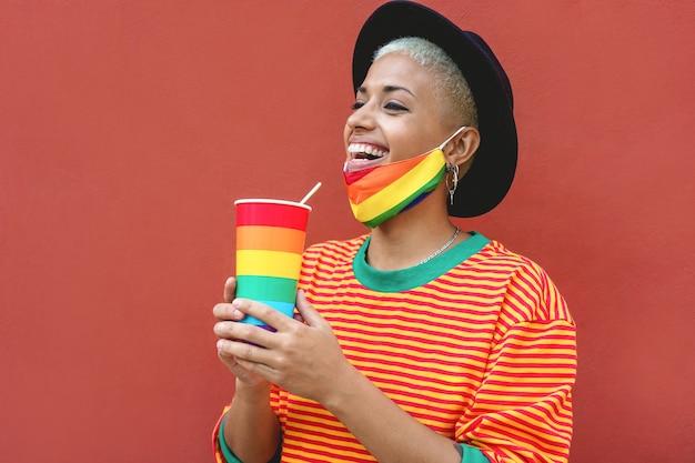 Glückliche junge schwule frau, die von einem regenbogenglas trinkt, während sie eine stolzmaske trägt