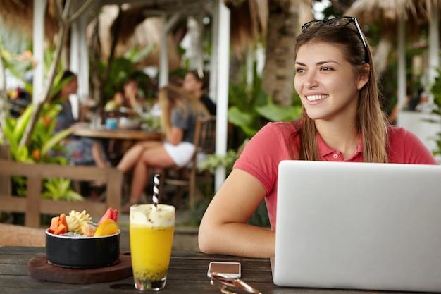Glückliche junge selbständige frau, die freie drahtlose internetverbindung genießt, die vor allgemeinem laptop im straßencafé sitzt. freudige frau, die notebook-computer während des mittagessens im bürgersteig-restaurant verwendet