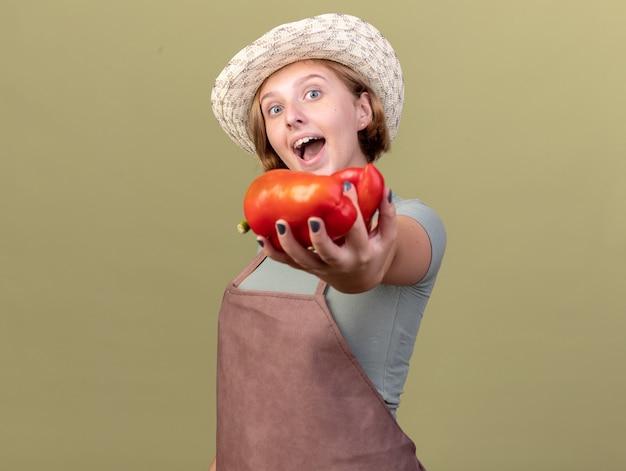 Glückliche junge slawische gärtnerin mit gartenhut mit rotem paprika
