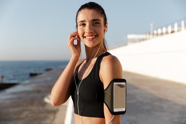 Glückliche junge sportfrau, die musik draußen hört.