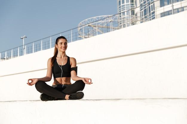 Glückliche junge sportfrau, die musik hört, machen yogaübungen.