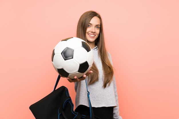 Glückliche junge sportfrau über dem lokalisierten rosa, das einen fußball hält