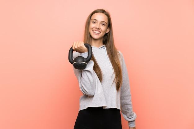 Glückliche junge sportfrau über der lokalisierten rosa wand, die das gewichtheben mit kettlebell macht
