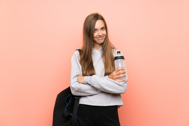 Glückliche junge sportfrau über lokalisierter rosa wand mit einer flasche wasser