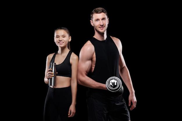 Glückliche junge sportlerin mit flasche wasser und muskulösem mann mit langhantel stehend