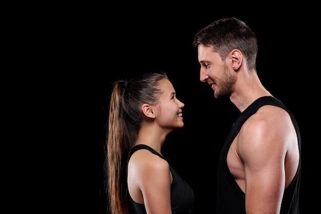 Glückliche junge sportlerin und sportlerin in aktivkleidung, die sich mit einem lächeln ansehen