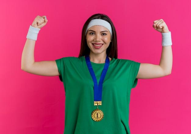 Glückliche junge sportliche frau, die stirnband und armbänder mit medaille um den hals trägt und starke geste tut