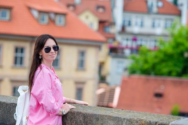 Glückliche junge städtische frau in der europäischen stadt auf der berühmten brücke. kaukasischer tourist, der entlang die verlassenen straßen von europa geht. früher morgen des warmen sommers in prag, tschechische republik
