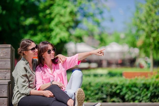 Glückliche junge städtische mädchen in der europäischen stadt. kaukasische touristen, die spaß zusammen draußen haben