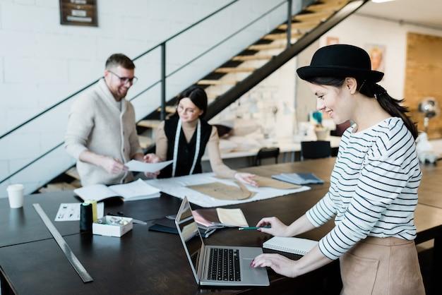 Glückliche junge stilvolle frau in hut und freizeitkleidung, die laptopanzeige beim stehen durch tisch in der werkstatt betrachtet