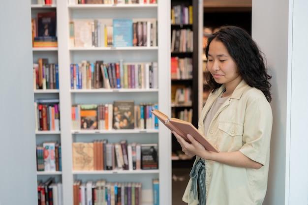Glückliche junge studentin, die text im offenen buch betrachtet