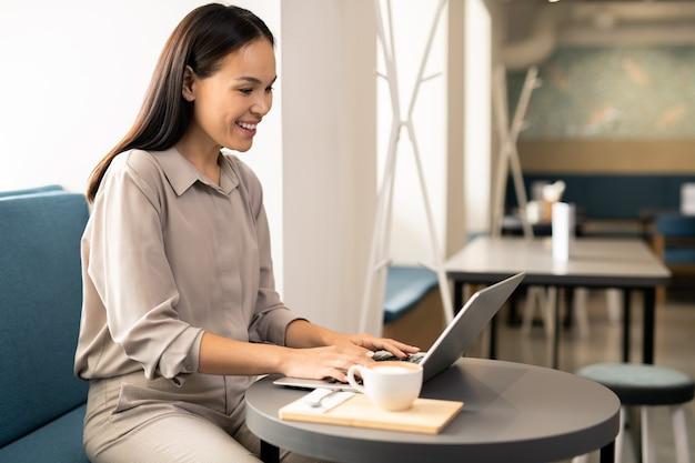 Glückliche junge studentin im intelligenten lässigen sitzen am tisch im café