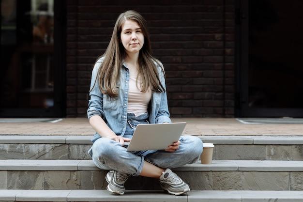 Glückliche junge studentin oder freiberuflerin, die an einem laptop arbeitet