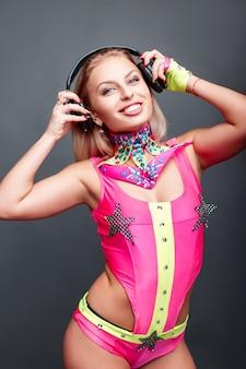 Glückliche junge tänzerin mit kopfhörern im rosa go-go-kostüm, das musik auf grau hört. partygirl