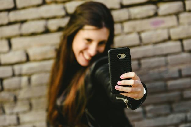 Glückliche junge tausendjährige frau, die selfies zu sich macht, während sie davon träumt, mit dem jungen zu flirten, in den sie sich verliebt, wenn sie die fotos in soziale netzwerke lädt.