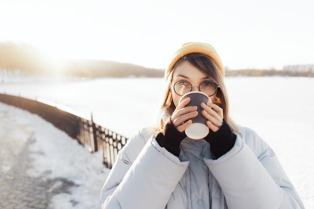 Glückliche junge teenagerfrau, die eine kaffeetasse zum mitnehmen hält