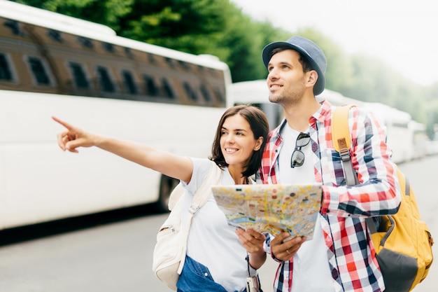 Glückliche junge touristische wanderer, die nach der richtung, nach platz suchend suchen, wohin man geht. europäische paare, die ferien haben, im stadtplan schauen und auf das bestimmungsort zeigen und erforschen neue standorte