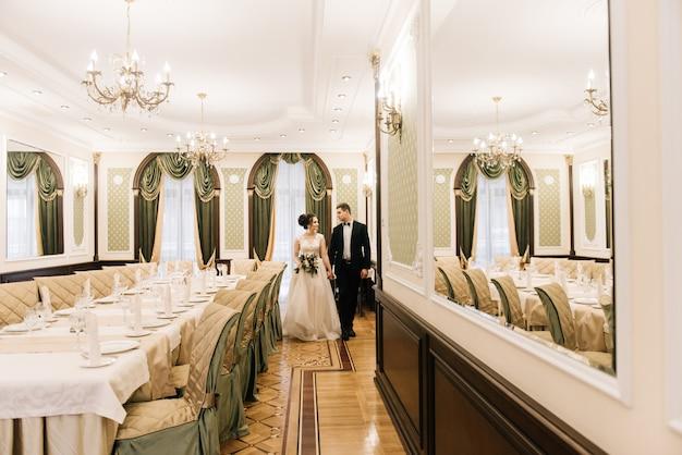 Glückliche junge und liebevolle braut und bräutigam gehen in den bankettsaal eines luxushotels. hochzeitstag