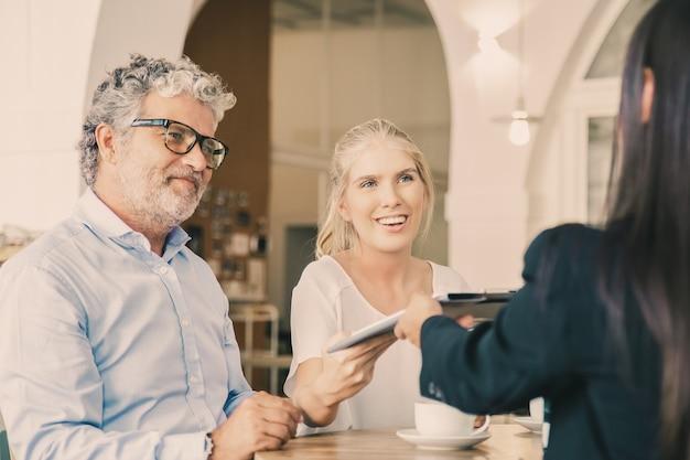 Glückliche junge und reife kunden treffen sich mit der agentin und geben ihr einen unterschriebenen versicherungsvertrag