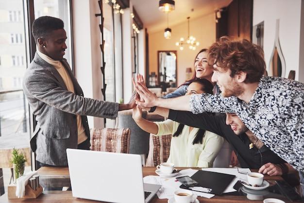 Glückliche junge unternehmer in der zufälligen kleidung am cafétisch oder im geschäftslokal, die sich hohe fünf geben, als ob sie erfolg feiern oder neues projekt beginnen