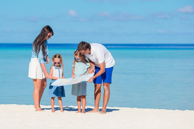 Glückliche junge vierköpfige familie mit karte auf dem strand