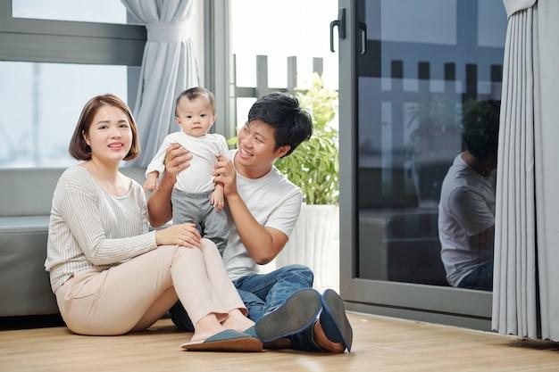 Glückliche junge vietnamesische familie mit dem kleinen baby, das zu hause auf dem boden sitzt
