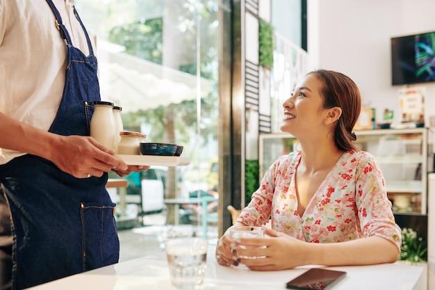 Glückliche junge vietnamesische frau, die kellner betrachtet, der ihren frischen laktosefreien joghurt und die cornflakes bringt