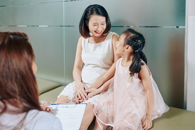 Glückliche junge vietnamesische mutter und tochter, die kinderarzt im krankenhaus besuchen
