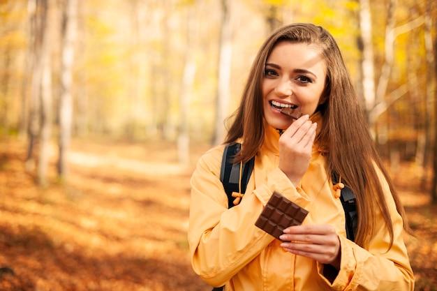 Glückliche junge wanderfrau, die schokolade isst