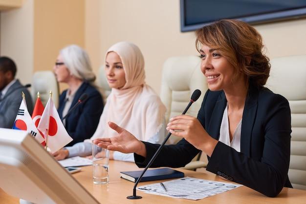Glückliche junge weibliche delegierte in der abendgarderobe, die publikum ansieht, während sie antwort auf eine frage nach rede gibt