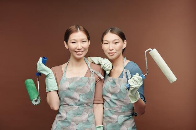 Glückliche junge weibliche zwillinge in schürzen und handschuhen, die farbroller halten, während sie vor der kamera nahe beieinander stehen und dich ansehen