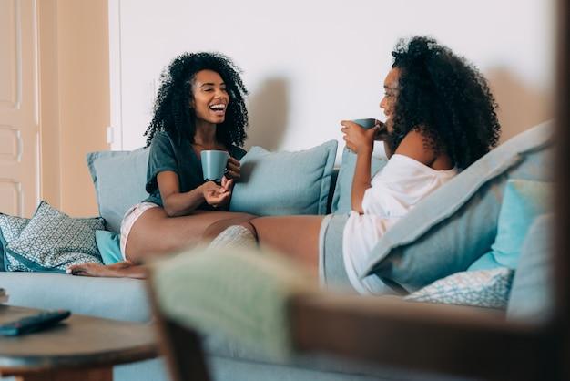 Glückliche junge zwei schwarze frauen, die im trinkenden kaffee der couch sitzen