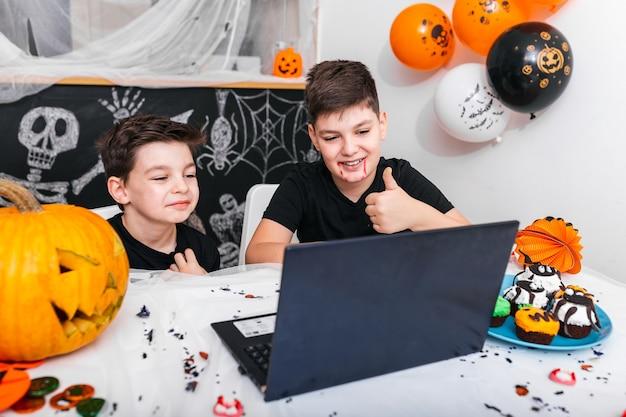 Glückliche jungen, brüder, die mit großeltern oder freunden per videoanruf unter verwendung eines laptops am halloween-tag sprechen, aufgeregte jungen in kostümen, die computer betrachten daumen zeigen