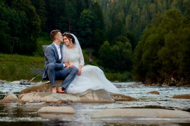 Glückliche jungvermählten, die auf einem felsen stehen
