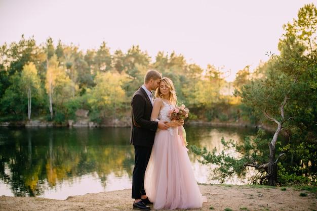 Glückliche jungvermählten, die bei sonnenuntergang stehen