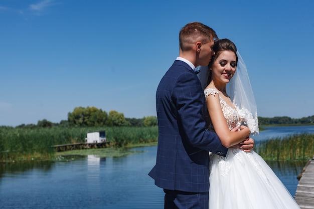 Glückliche jungvermählten, die leicht küssen und umarmen. porträt ein hochzeitspaar, das auf holzbrücke nahe fluss aufwirft.