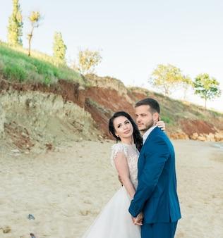 Glückliche jungvermählten stehen händchen haltend auf dem hintergrund des blauen meeres. hochzeitsspaziergang am sandstrand. im hintergrund blauer himmel
