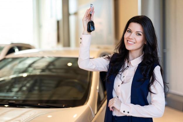 Glückliche käuferin, die mit schlüsseln nahe ihrem neuen fahrzeug im autohaus besitzt