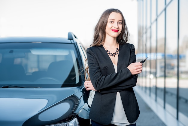 Glückliche käuferin, die schlüssel in der nähe des autos vor dem modernen avtosalon-gebäude hält