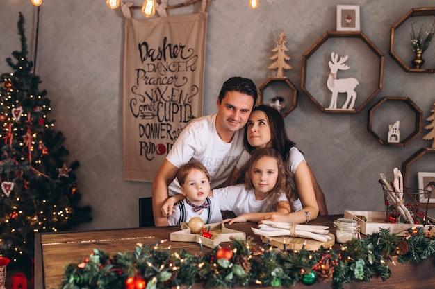 Glückliche kakasische familie im gemütlichen ferienhaus, das in den weihnachtslichtern verziert wird. fröhliche kinder und eltern feiern traditionelle feiertage