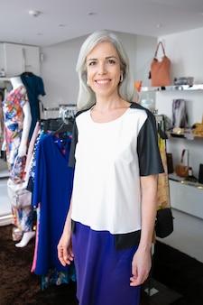 Glückliche kaukasische blonde frau mittleren alters, die nahe gestell mit kleidung im modegeschäft steht, kamera betrachtet und lächelt. boutique-kunden- oder verkäufer-konzept