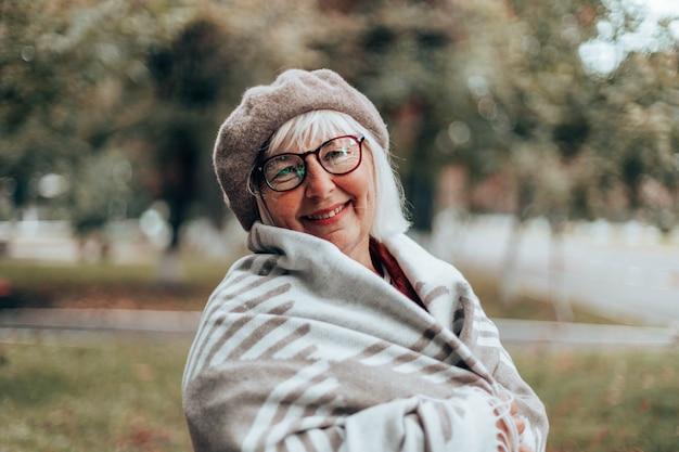 Glückliche kaukasische dame in der kuscheligen decke der stilvollen baskenmütze auf einem spaziergang an einem windigen tag im herbst oder herbst